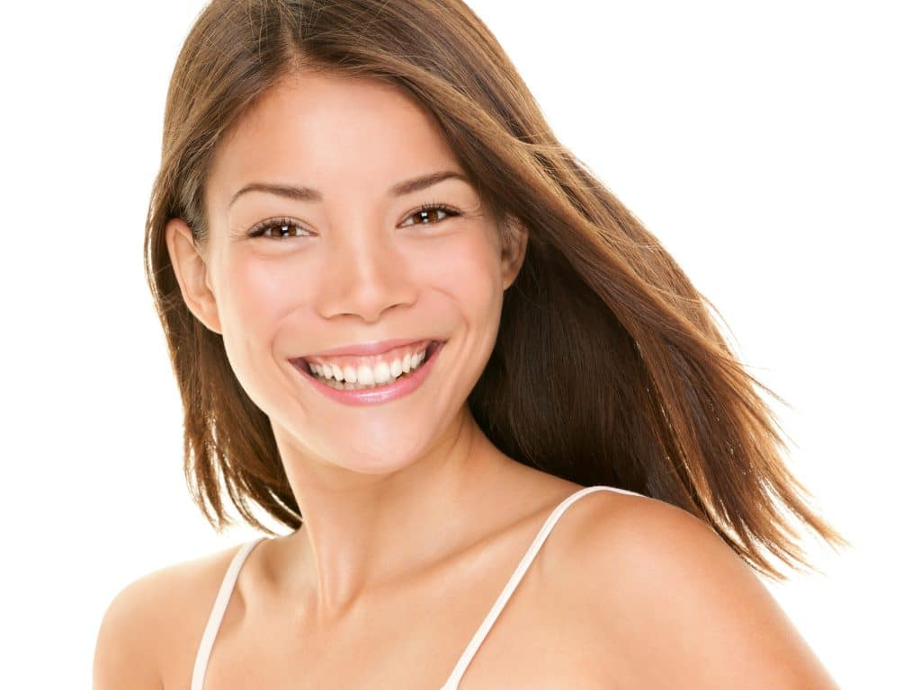 Natural smile. Woman smiling happy - portrait of joyful content girl with big smile. Mixed race Asian Chinese / Caucasian female model in her twenties.