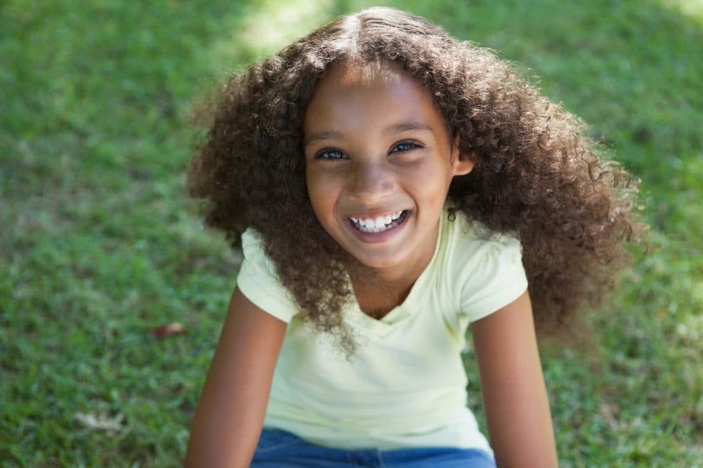 Young girl smiling at the camera in the park on a sunny day